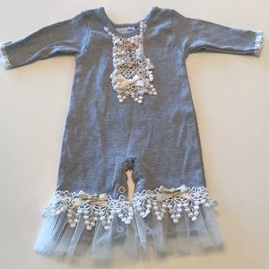 Gray onesie with ruffles and trim details.